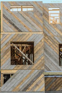 A building being framed and sided with the wood forming a angled pattern