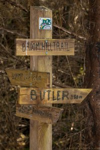 A wooden trail marker shows the distance