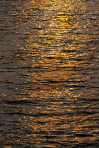 the setting sunlight casts shadows and an orange glow over the waves