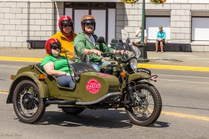 a motorcycle with sidecar and three large occupants