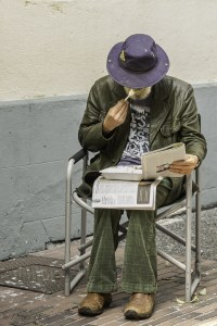 man eating lunch on his lap while reading the paper