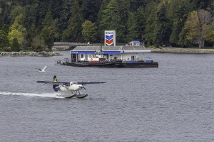 float plane taxiing past the floating Chevron station