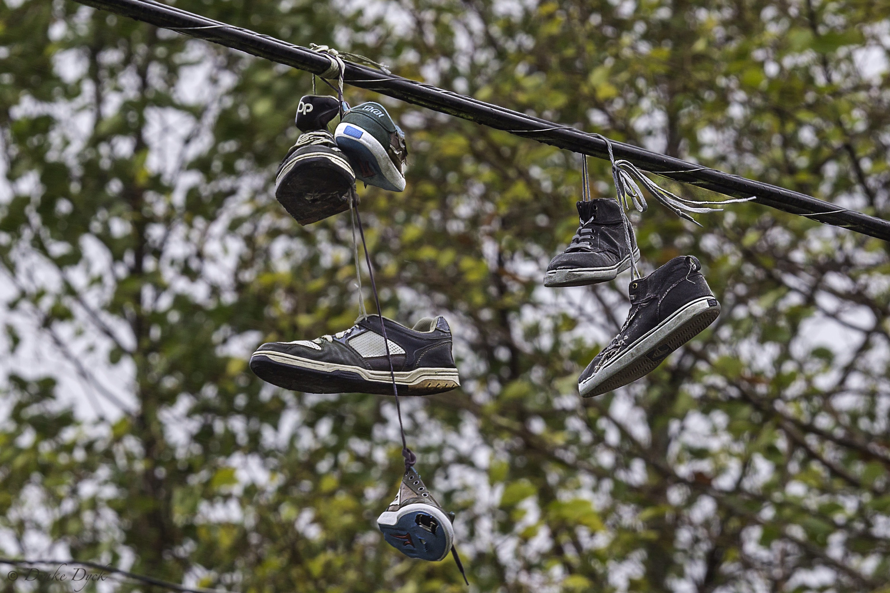 three pairs of shoes hanging from a line