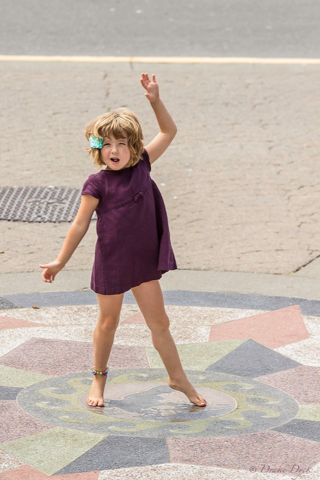 a little girl in a dress spins around in a circle