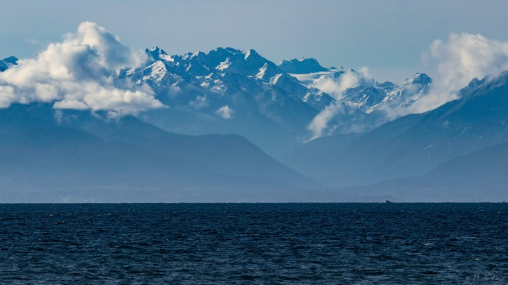 view from Ogden Point of the snow capped mountains and ocean