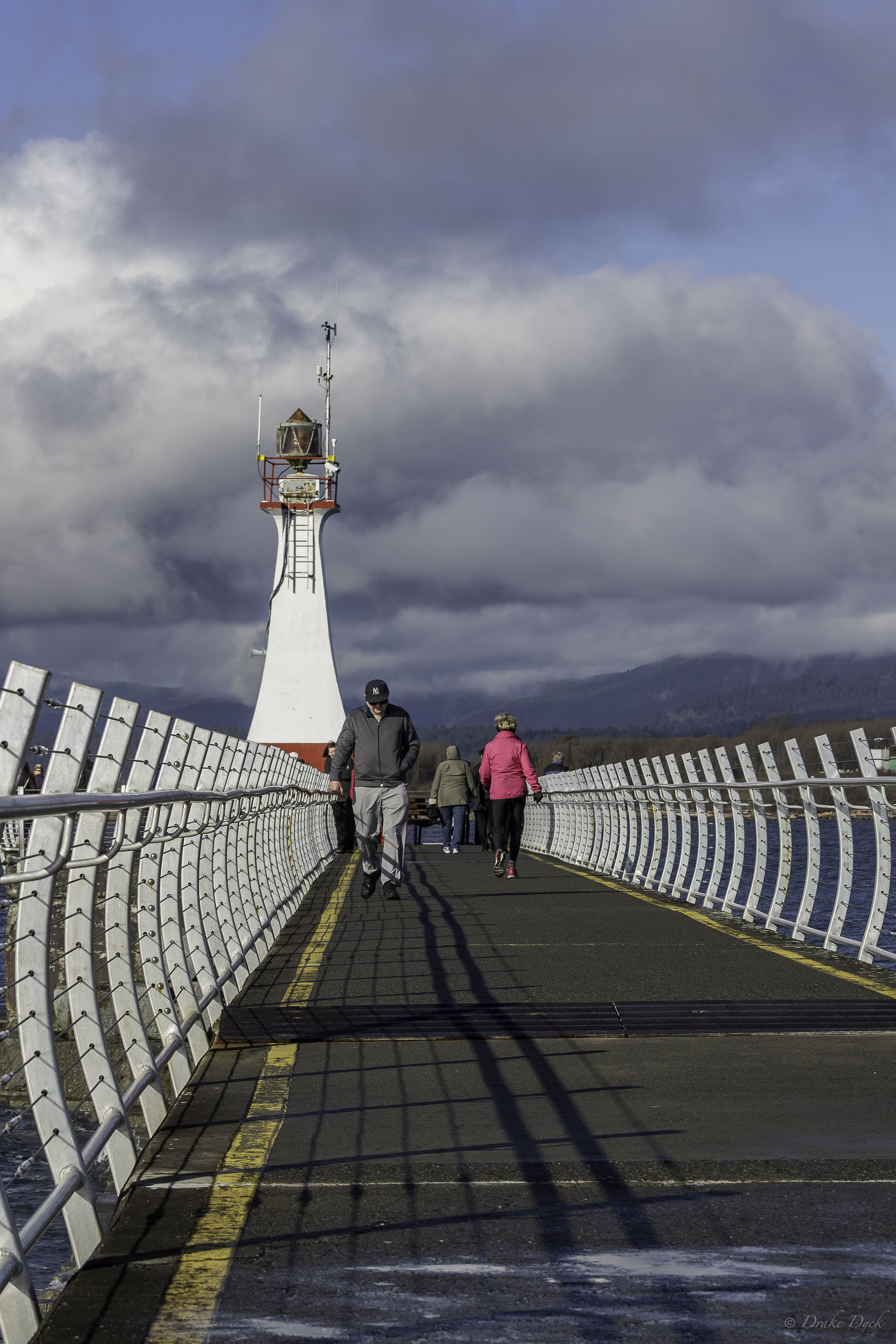silver rails line the path to the lighthouse at the end of the breakwater