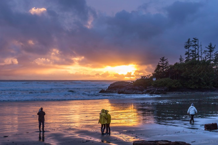 people standing on the beach watching a spectacular sunset