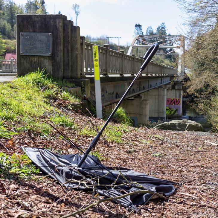 a broken umbrella lies next to the Sooke River bridge