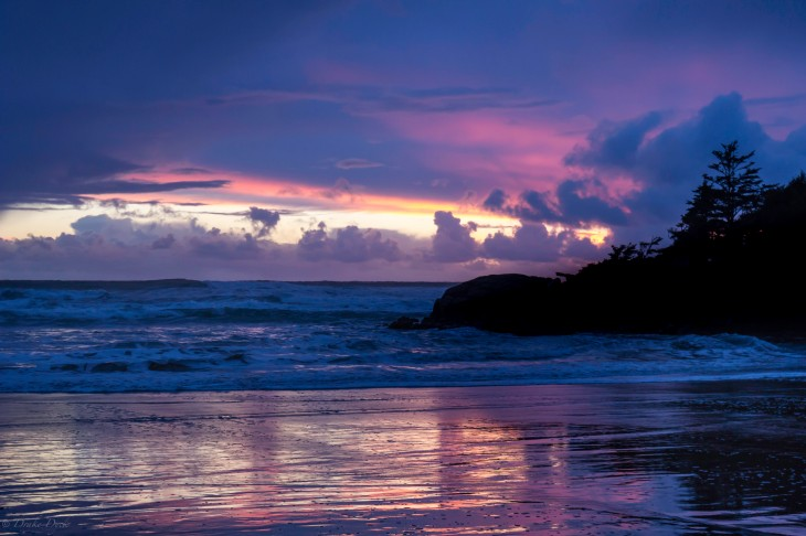 Purples and oranges colour the sky and beach