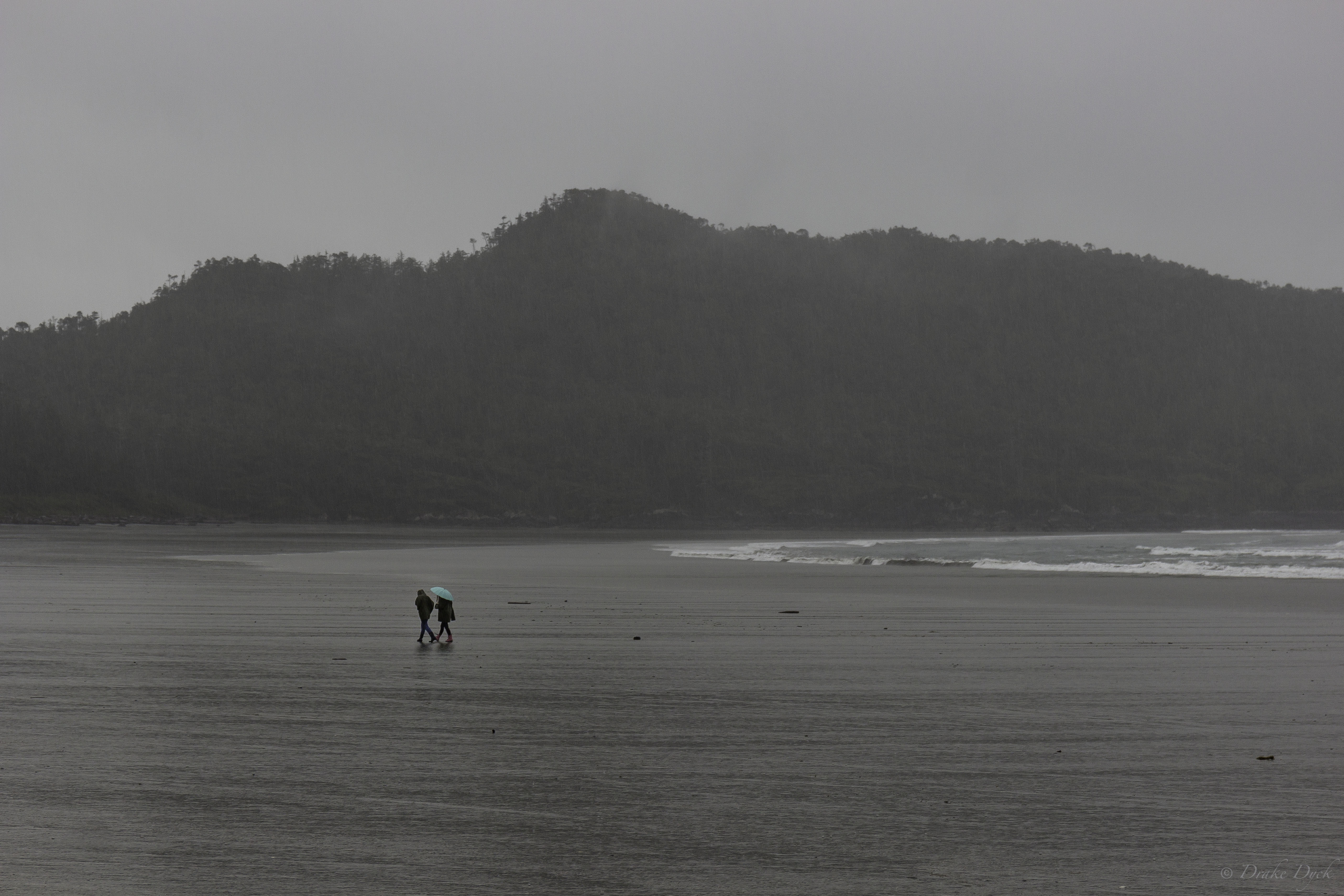 a couple with a colourful umbrella walk in a downpour on the beach
