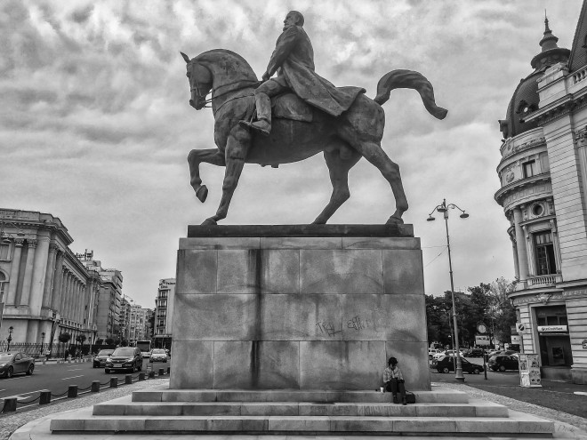 a woman reading a book sits at the base of a giant statue of a man on a horse