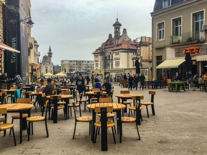 pedestrians, tables and shops line the street in Constanta Romania