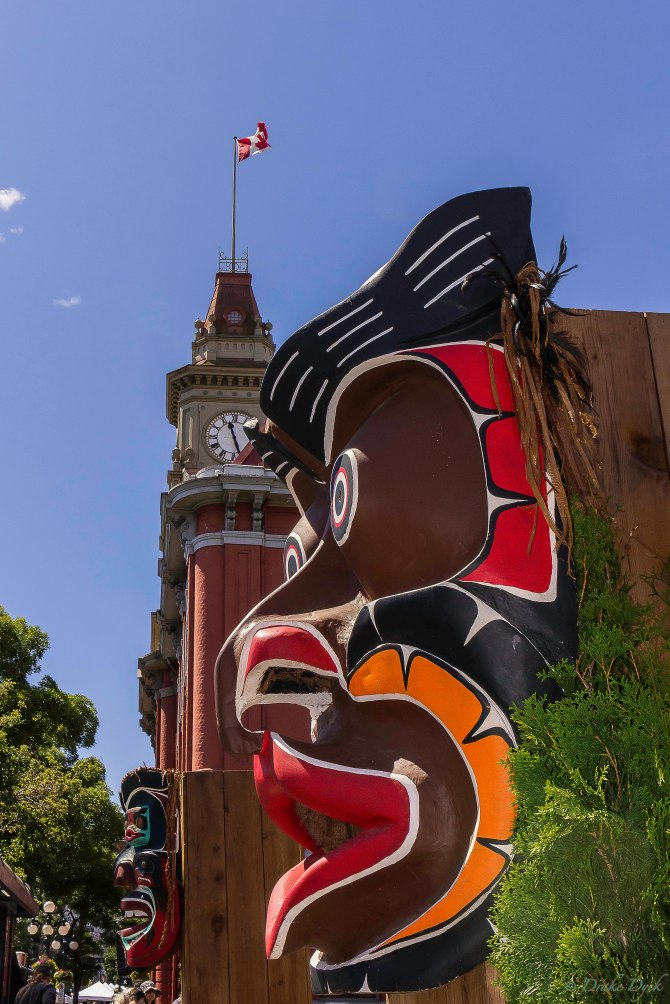 a colourful carved wooden mask with city hall and trees in the background