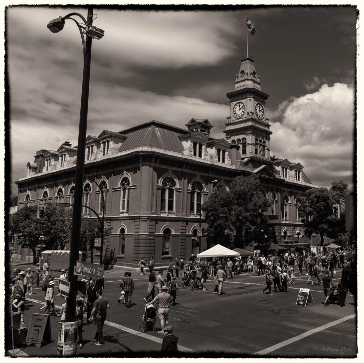 a sepia look at YYJ city hall with pedestrians wandering down Douglas Street