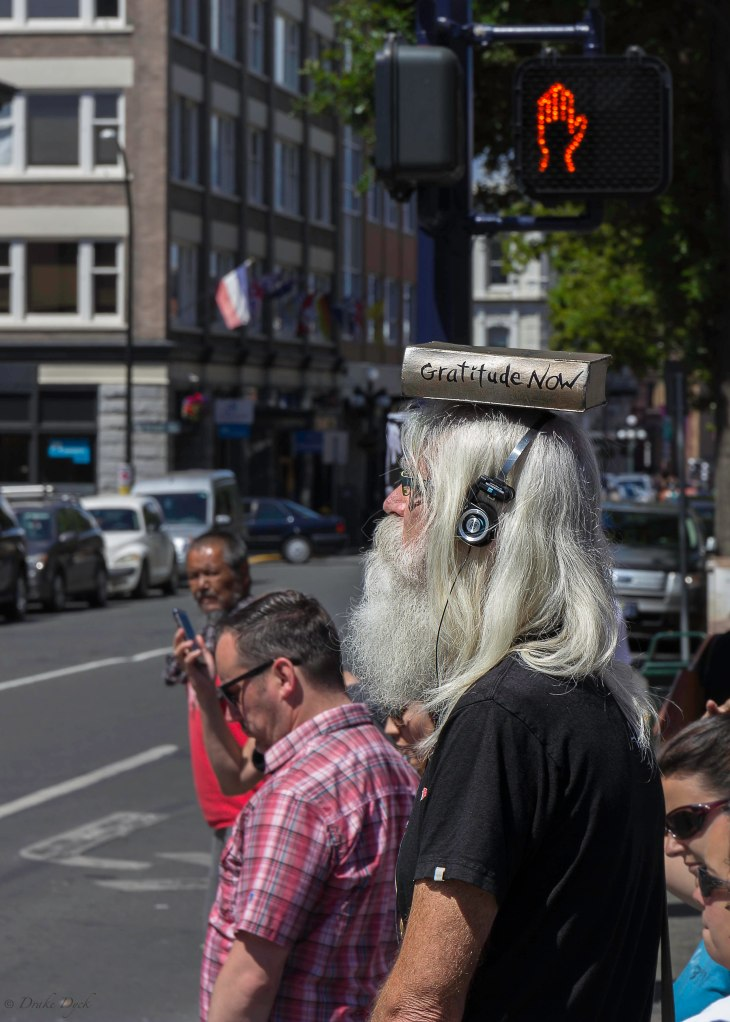 grey haired man with headphones and Gratitude Now book on his head walks past a Do Not Cross hand sign