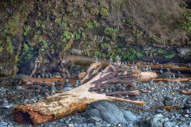 Stacked rocks sit atop driftwood logs