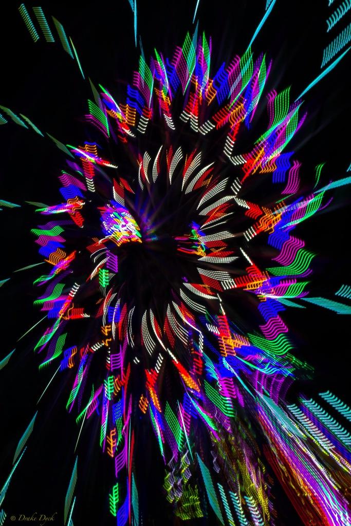 pinwheel looking lights of a ferris wheel at night