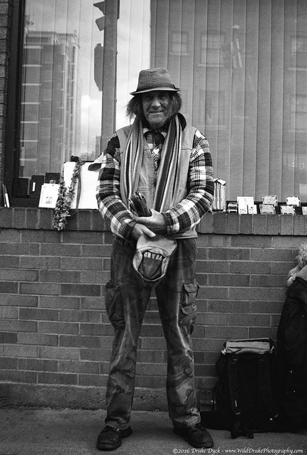 man standing with two hats