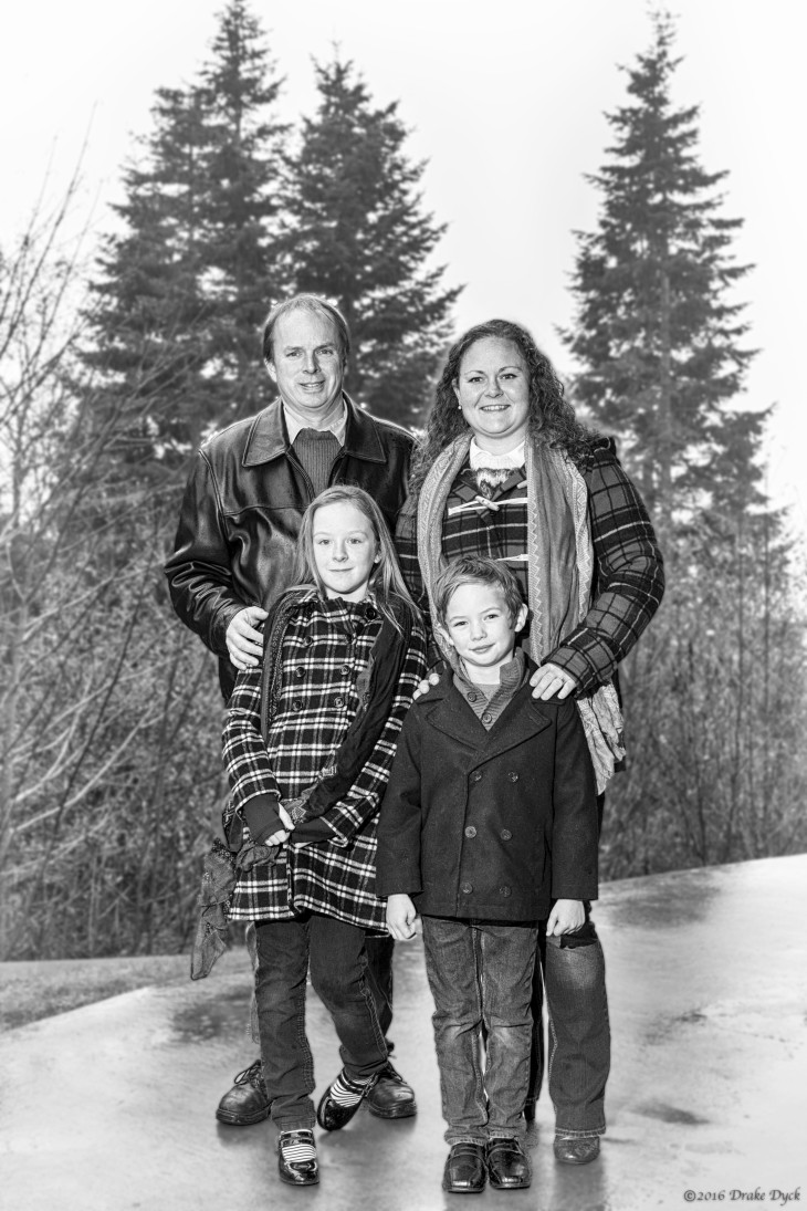 family of four in black and white in front of trees
