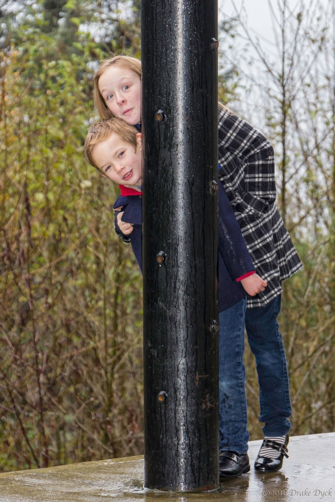 two children peeking out from behind a pole