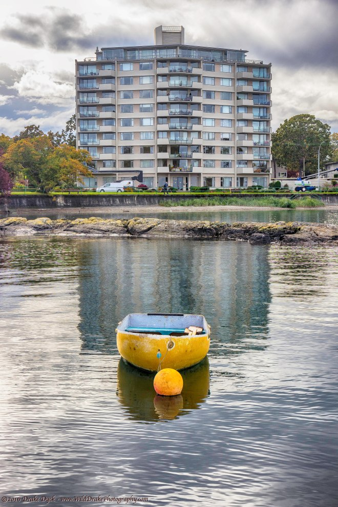 a yellow boat floats in front of an apartment building