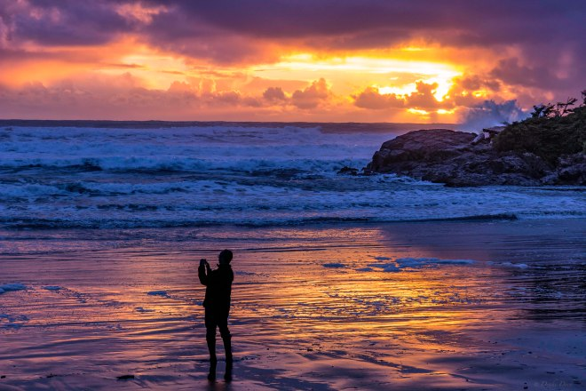 man taking pictures on a beach during sunset