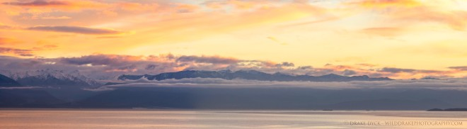 a cloudy mountain sunset over the ocean