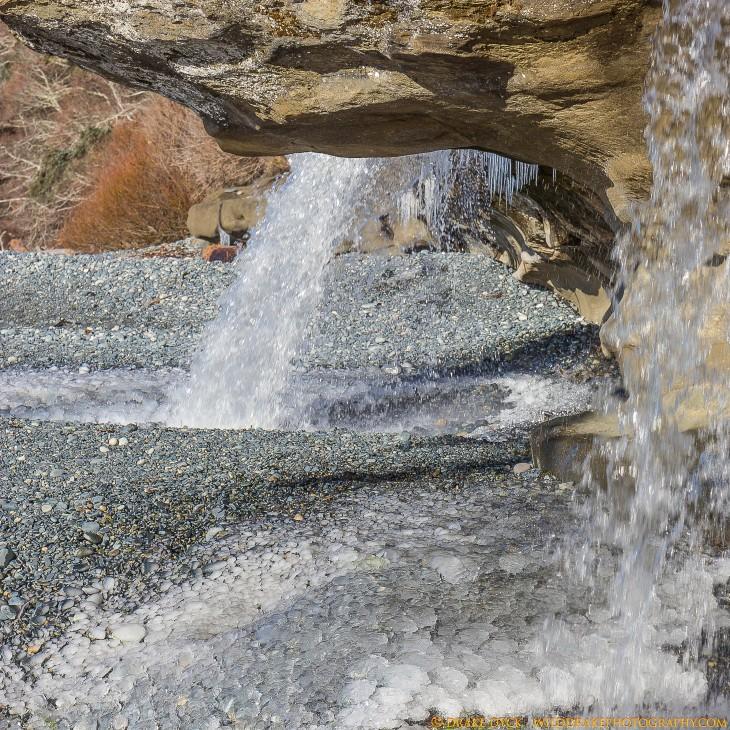 Waterfall on a frozen rocky beach