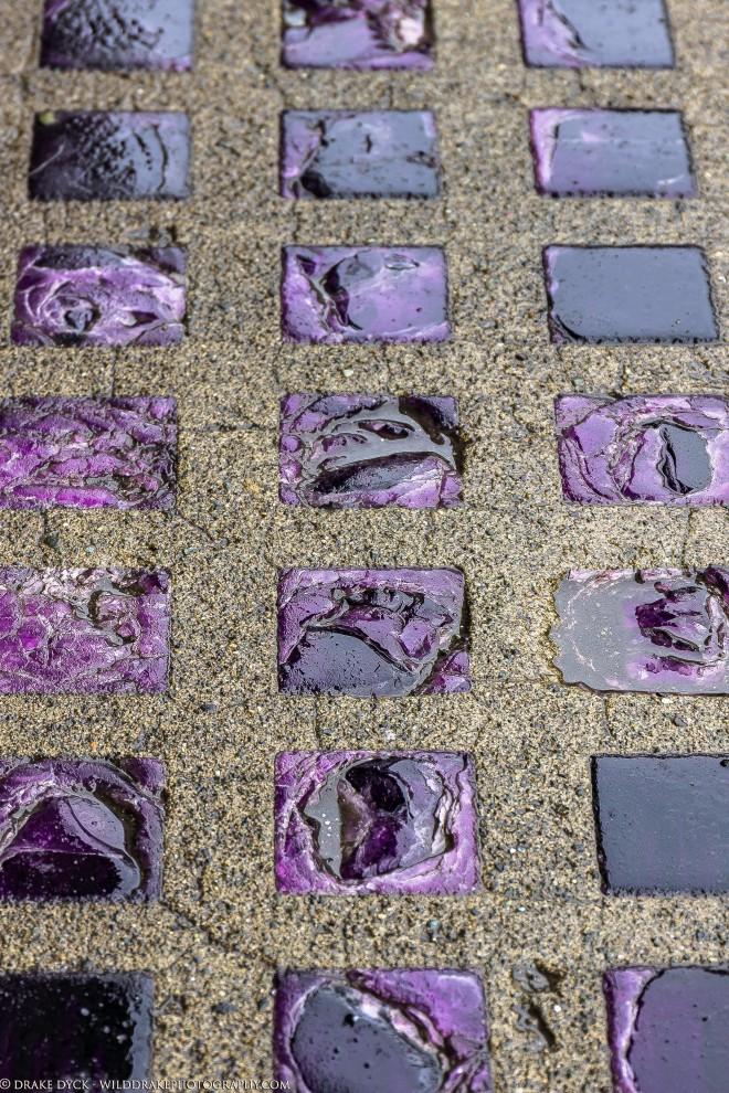 Purple rock squares inlaid in the sidewalk