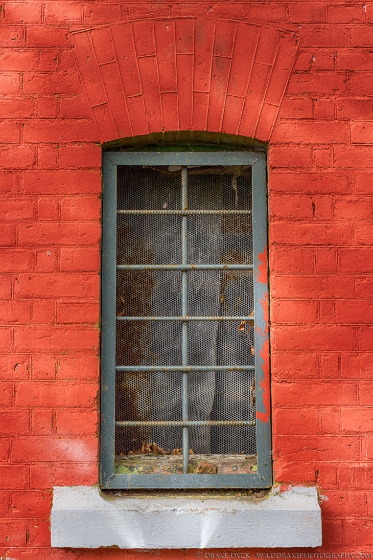 red painted brick and an iron bar window
