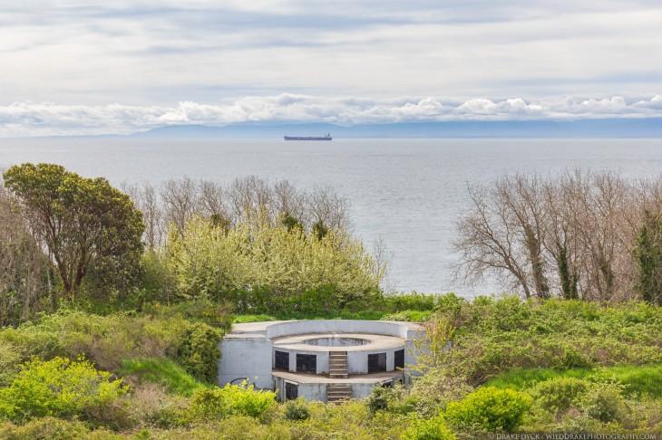 a naval gun emplacement overlooks a freighter at sea