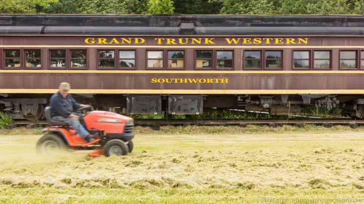 a Grand Trunk Western Southwork rail car is passed by a riding lawnmower