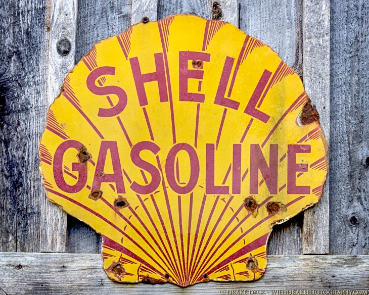 red and yellow Shell Gasoline sign with bullet holes