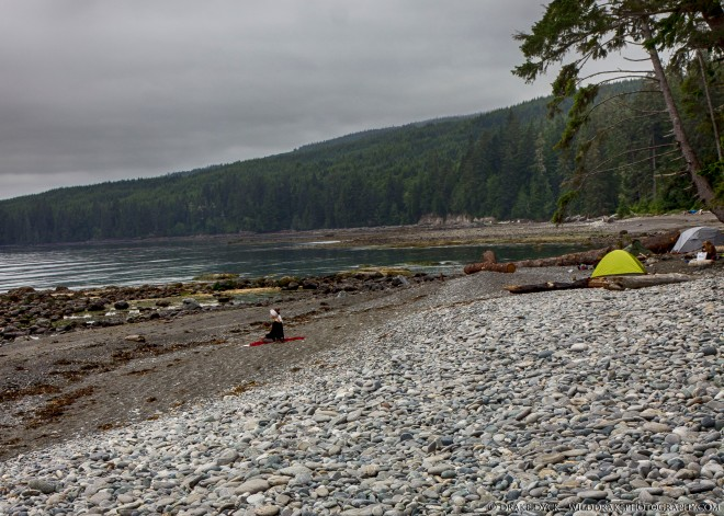 a hiker meditates on the beach near some tents