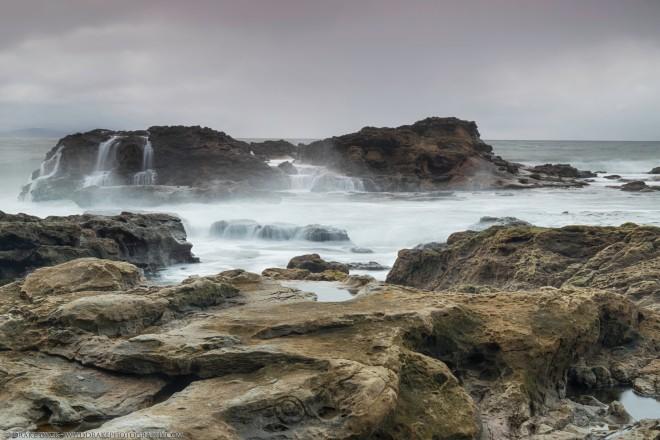 stormy seas bash a rocky island