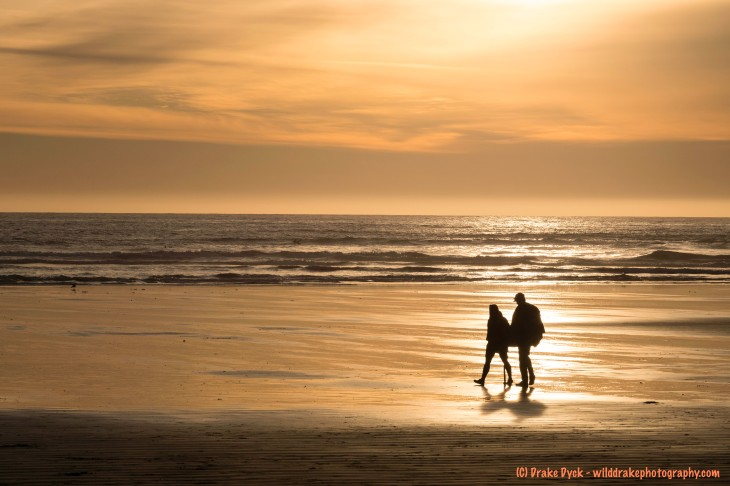 two people silhouetted in the reflection of a golden sunset