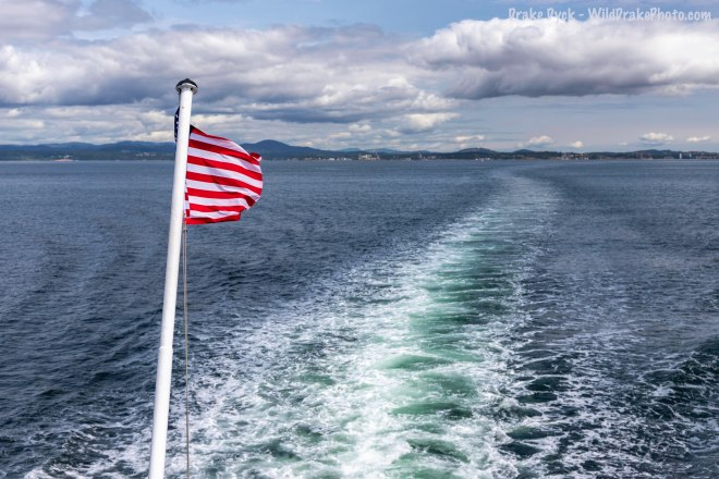 US flag waves on back of ferry across the Jaun de Fuca straight