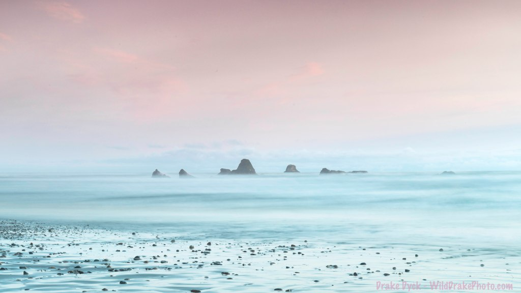 several sea sacks appear to rise out of the misty sea in a pastel sunset