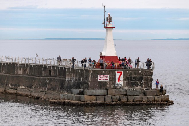 a small lighthouse on the breakwater surrounded by people