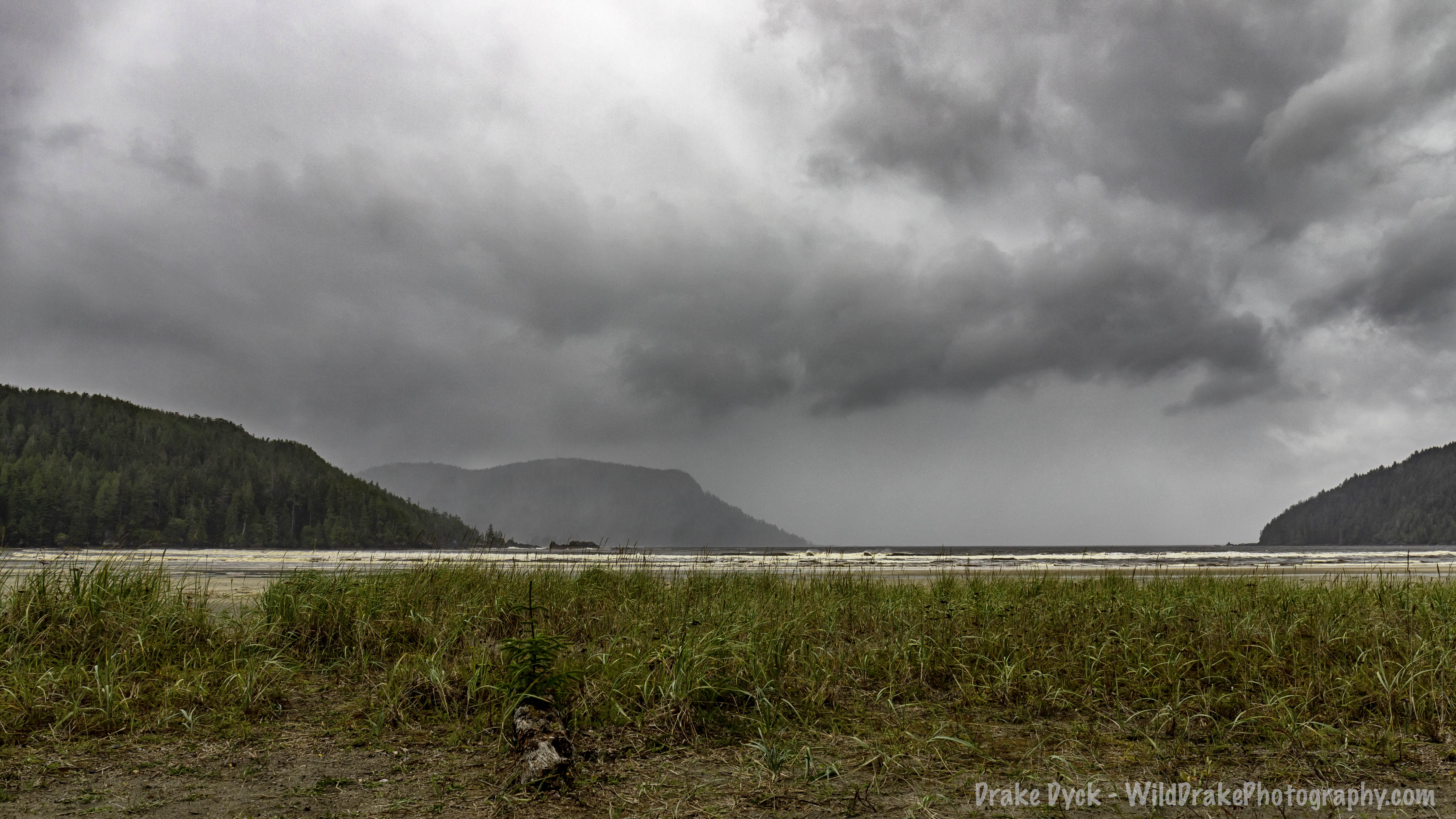 menacing dark grey clouds and misty rain over the treed slopes of Cape Scott Provincial Park