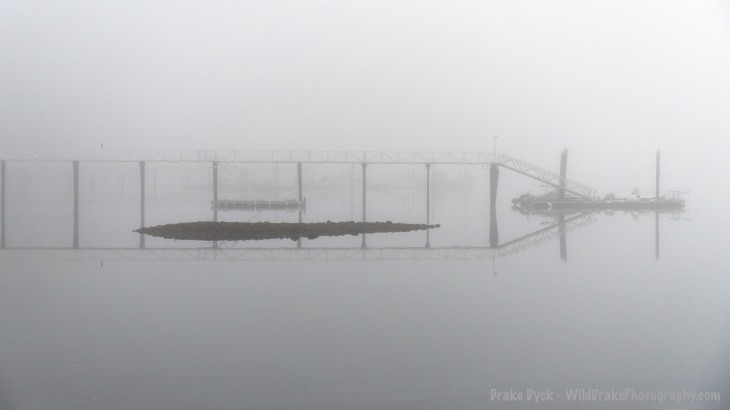 fog enshrouds a pier and rocks
