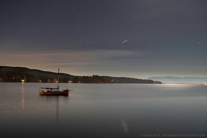 a meteorite can be seen streaking above a sailboat in the Sooke harbour