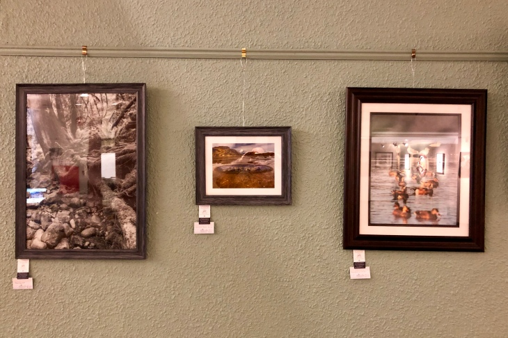 A trio of photos hanging on display